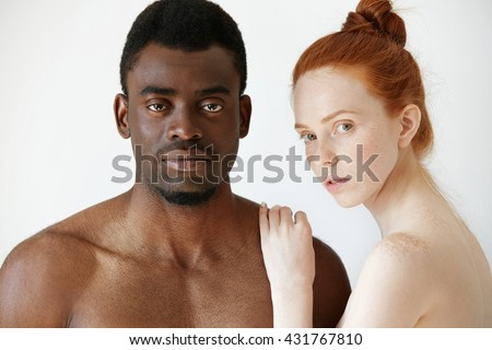Pure unconditional love: beautiful Caucasian young woman with red hair and freckles embracing her naked African boyfriend or husband, both looking at the camera. Interracial relationships concept - stock photo
