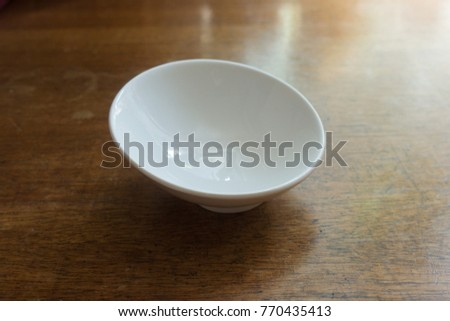 Pure white empty porcelain bowl on wooden table