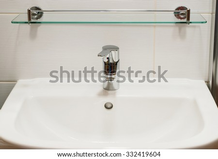 Pure white sink and chrome faucet with handle. Bathroom detail.