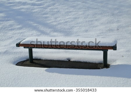 Pure white snow is piled up bench.