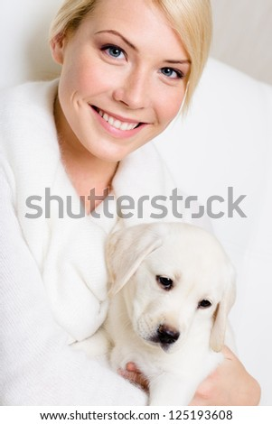 Purebred puppy sitting on the hands of woman