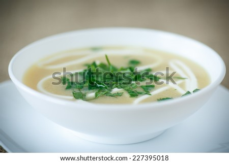 puree soup with greens and sour cream in a white plate - stock photo
