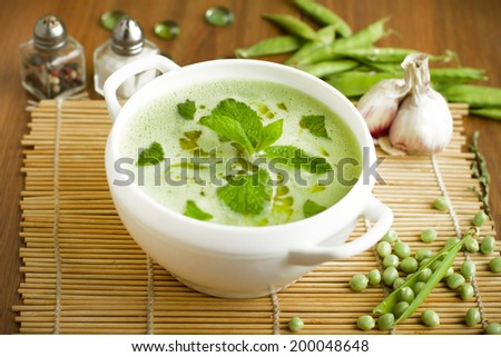 Pureed pea soup with spices, fresh mint and garlic (vegan, vegetarian) - stock photo