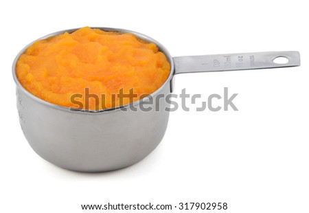 Pureed pumpkin in an American measuring cup, isolated on a white background - stock photo