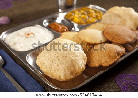 Puri, a type of fried bread from India, closeup on a food thali or steel platter