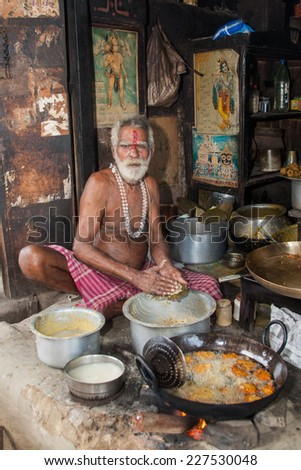 PURI, INDIA  OCTOBER 9th 2010 An old man fries food in a wok in a roadside stall in East India.  - stock photo
