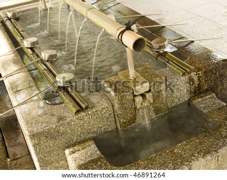Purification fountain at entrance to Shinto  Shrine, Japan.  worshipers cleanse hands and mouth before entering shrine - stock photo