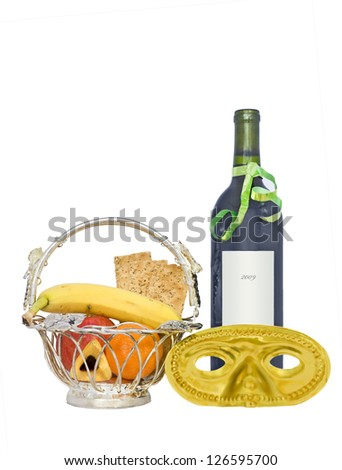 Purim basket, wine, mask isolated on white.A custom is to send gifts of food and drink called Mishloach Manot, Shalach Manot.Shown is fresh fruit, crackers, hamantashen, wine bottle, and costume mask. - stock photo