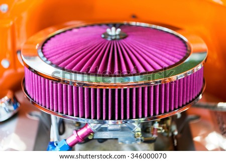 Purple air filter from a custom car in vivid colors and orange background. - stock photo