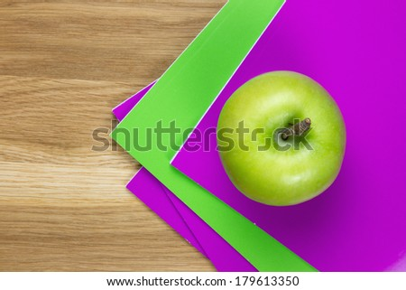 purple and green exercise-books with green apple on top of it on wooden desk - stock photo