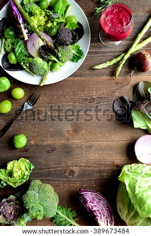 Purple and green spring vegetables salad,beet root juice and vegetables on the dark wooden background - stock photo