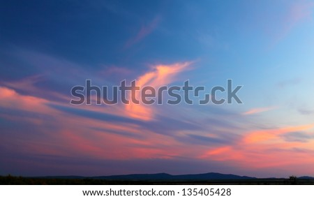Purple and pink clouds in the sky at sunset - stock photo