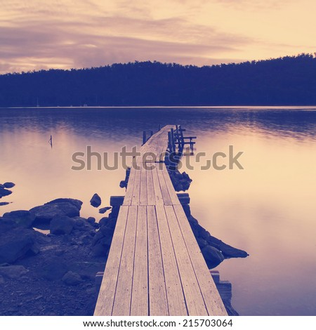 Purple and pink sunset over water and jetty with Instagram style filter - stock photo