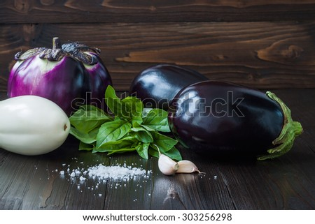 Purple and white eggplant (aubergine) with basil and garlic on dark wooden table. Fresh raw farm vegetables - harvest from the garden in rustic kitchen. Rural still life - stock photo