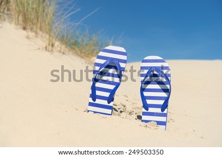 Purple and white striped flip flops in the dunes at the coast - stock photo