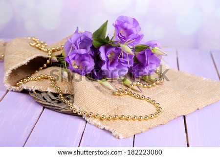 Purple artificial eustoma on sackcloth on color wooden  table, on bright background