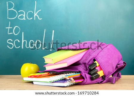 Purple backpack with school supplies on wooden table on green desk background - stock photo