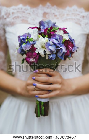 purple blue and white bride's bouquet in hands of bride