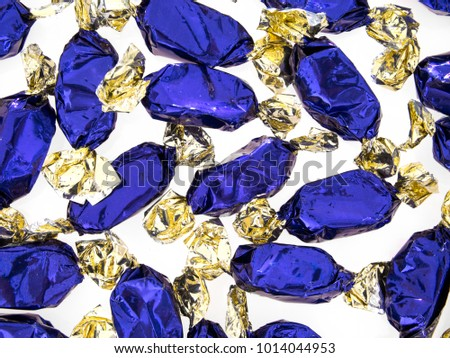 Purple blue foil wrapped toffee sweets on white. Closeup detail.