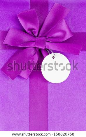 Purple bow on gift box using background - stock photo