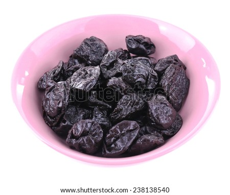 Purple bowl of prunes isolated on white - stock photo