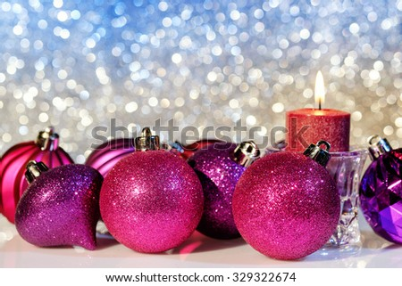 Purple Christmas balls and candle on a blur background close up. Selective focus.