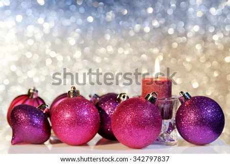Purple Christmas balls and candle on a blurred festive background, close up. Selective focus.
