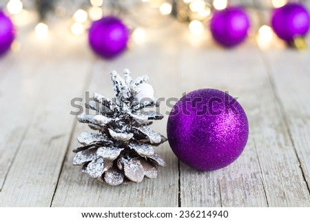 Purple christmas balls on with christmas lights in the background. - stock photo