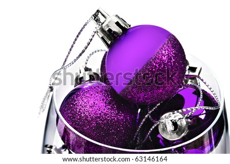 Purple  christmas baubles in a glass on a white background with space for text - stock photo