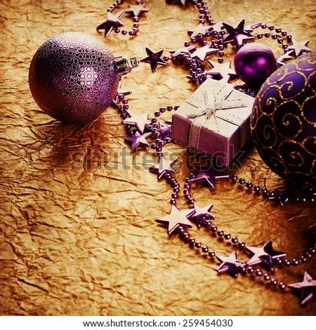 Purple christmas decoration on golden paper background - stock photo