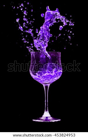 Purple cocktail glass splash out on a black background.