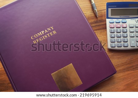 Purple Company Register binder with pen and calculator - stock photo