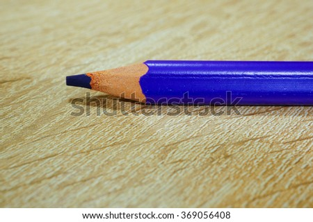 Purple drawing pencil on wooden background