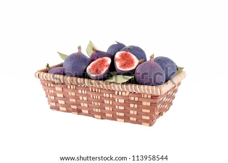 purple figs in a straw basket, isolated on white
