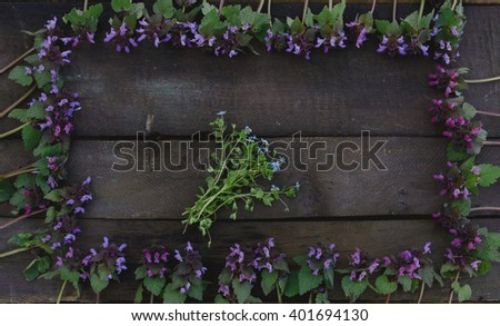 Purple flowers forming a frame and forget-me-nots in the middle on wooden board - flat lay