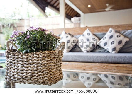 Purple flowers in a basket placed on a glass coffee table, decorative cushions and grey sofa in outdoor sitting area
