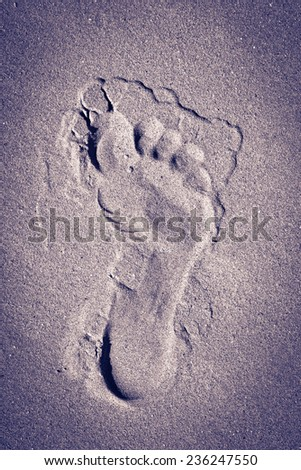 Purple footprint in the sand background