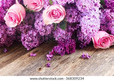 Purple fresh  Lilac flowers with pink rose flowers on wooden table   - stock photo