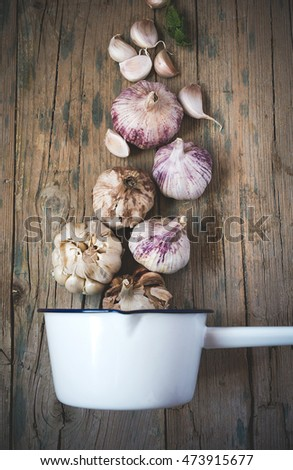 Purple garlics on a napkin on a rustic wooden table with thyme and parsley