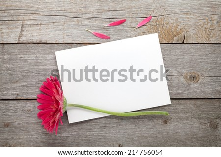 Purple gerbera flower and blank greeting card on wooden table - stock photo