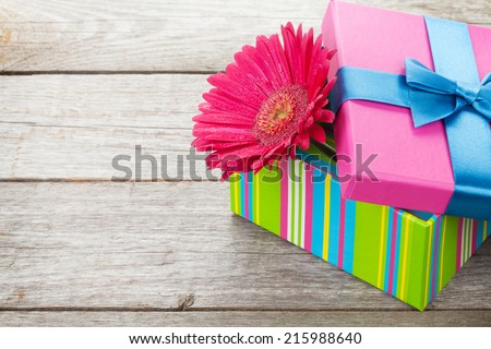 Purple gerbera flower in gift box on wooden table with copy space - stock photo