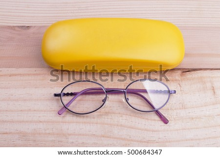 Purple glasses and a box placed on a wooden background.