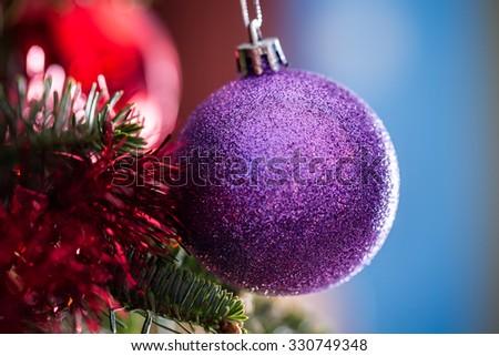 Purple glitter Christmas ornament hanging on a tree - stock photo