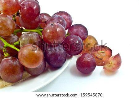 Purple grape in two white bowls isolated on white background.