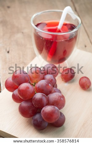 Purple grape juice in glass on a wood cutting boards.