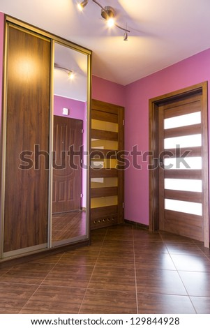 Purple hall interior with wardrobe and brown tiles - stock photo