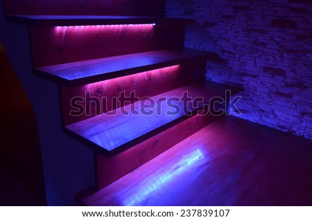 Purple illuminated wooden stairs and rough stone wall
