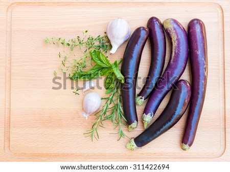 Purple japanese eggplants with herbs and garlic on wooden cutting board. - stock photo