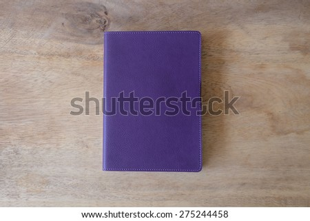 Purple leather notebook on wooden table, the personal organizer - stock photo