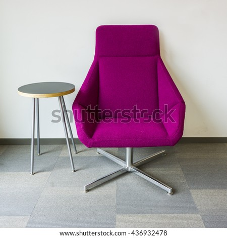 Purple lounge chair and side table on square patterned grey carpet - stock photo